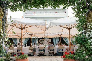 Dining table terrace parasols at beach wedding venue Italy