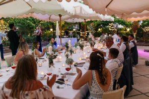Guests dining on terrace at beach destination wedding
