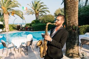 saxophone player by pool at luxury wedding destination Italy