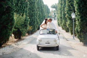 couple kiss Fiat500 wedding car treelined venue Italy