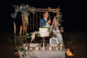 couple cutting wedding cake beach venue Italy