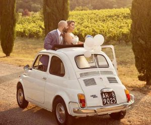 Wedding couple in white Fiat 500 amongst the vineyards at Villa la Selva wine resort Tuscany